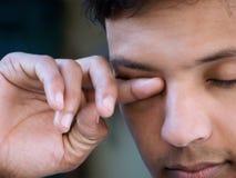 Olhos asiáticos da fricção do homem imagens de stock royalty free