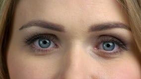 Olhos azuis bonitos do fim da jovem mulher acima vídeos de arquivo