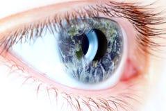 Olhos azuis no macro com mapa da terra Imagens de Stock Royalty Free
