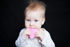 Olhos de azuis bebés, comendo o brinquedo Imagem de Stock