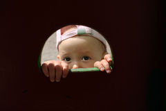 Olhos de Childs que olham através do furo Foto de Stock