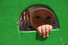 Olhos de Childs que olham através do furo Fotografia de Stock