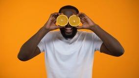 Olhos de fechamento do homem afro-americano alegre com metade das laranjas, vitaminas para a saúde video estoque