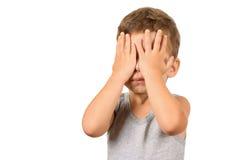 Olhos de fechamento do menino com mãos Fotografia de Stock Royalty Free