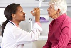 Olhos do doutor Examining Superior Fêmea Paciente fotografia de stock