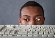 Olhos do homem acima do teclado fotografia de stock royalty free