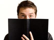 Olhos do homem surpreendido acima do livro preto Fotografia de Stock Royalty Free