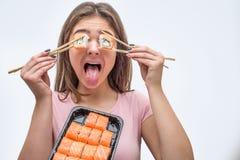 Olhos engraçados da tampa da jovem mulher com partes do sushi Guarda-os com hashis O prato com rolos é na frente dela fotografia de stock