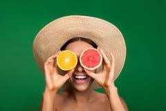 Olhos escondendo da menina alegre atrás dos frutos Imagem de Stock