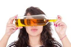 Olhos escondendo da menina latino atrás de uma garrafa amarela Foto de Stock Royalty Free