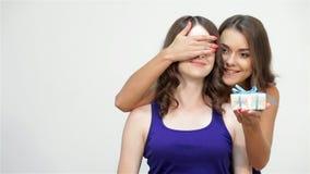 Olhos fêmeas da irmã da coberta que guardam um presente vídeos de arquivo