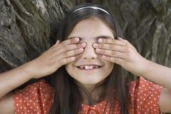 Olhos felizes da coberta da menina pela árvore Foto de Stock