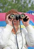 Olhos largos espiando binoculares fotografia de stock