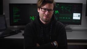 Olhos maliciosos do bandido do hacker que olham quando a câmera se mover nele, contra os monitores do computador do trabalho do f vídeos de arquivo