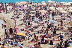 Olidaymakers zonnebaadt op strand in Barcelona Stock Afbeeldingen