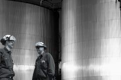 Olie-arbeiders en industriële brandstoftanks bij zonsondergang Stock Foto's