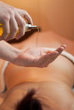 Olie die wordt gegoten om een vrouw te masseren Royalty-vrije Stock Afbeeldingen