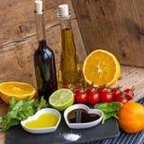 Olie en azijn in hart gevormde die kommen met verse produ worden getoond Stock Foto