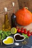 Olie en azijn in hart gevormde die kommen met verse produ worden getoond Stock Foto's