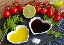 Olie en azijn in hart gevormde die kommen met verse produ worden getoond Stock Fotografie
