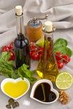Olie en azijn in hart gevormde die kommen met verse produ worden getoond Royalty-vrije Stock Afbeelding