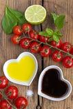 Olie en azijn in hart gevormde die kommen met verse produ worden getoond Stock Afbeelding