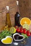 Olie en azijn in hart gevormde die kommen met verse produ worden getoond Stock Afbeeldingen