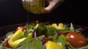 Olie het gieten over gemengde salade stock video