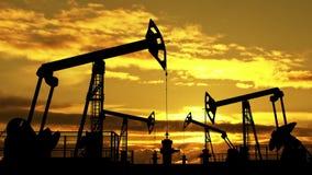 Olie pumpjacks tegen oranje schemer stock video