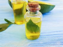Olie, verse avocado op blauwe houten aromatisch stock afbeeldingen