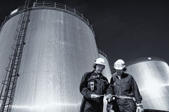 Oliearbeider met raffinaderij en brandstoftanks Stock Foto's
