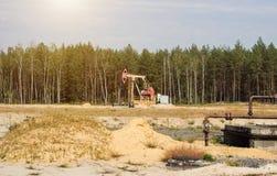 Oliebron voor de extractie van olie en benzine en gas op de achtergrond van het bos, de productie van brandstof-brandbaar stock afbeelding