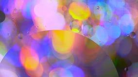 Oliecirkels in water op een gekleurde achtergrond stock video