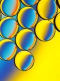 Oliedruppeltjes in water met kleurrijke achtergrond Stock Afbeelding