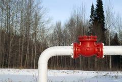 Olieleidingskromming tegen een achtergrond van een vaag bos de winterlandschap Stock Afbeeldingen
