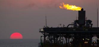 Olieplatform en gloed bij zonsondergang stock foto