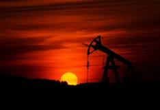 Oliepomp en zonsondergang Stock Foto
