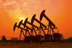 Oliepomp tegen het plaatsen van zon Stock Afbeeldingen