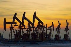 Oliepomp tegen het plaatsen van zon Stock Fotografie