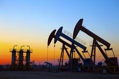 Oliepomp tegen het plaatsen van zon Stock Foto