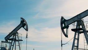 Oliepompen die aan een gebied werken Het de boortorenswerk van de metaalolie, pompende olie stock videobeelden
