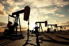 Oliepompen op de zonsonderganghemel Royalty-vrije Stock Foto's