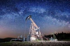 Oliepompen op het olieveld in de nacht stock foto's