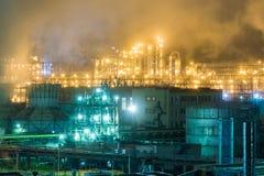 Olieraffinaderij met pijpen en distillatiecomplexen bij nacht Stock Foto's