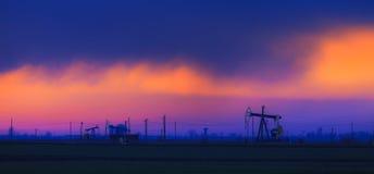 Olieveld met oliepompen en boorplatforms die op zonsonderganghemel worden geprofileerd Royalty-vrije Stock Afbeeldingen