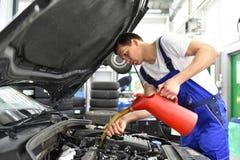 Olieverversing van de motor van een auto in een workshop door een professio stock afbeeldingen