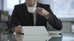 Oligarch het drinken koffie in zijn bureau en het lezen van tekst van contract voor het ondertekenen stock videobeelden