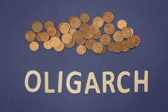 Oligarch written with wooden letters on a blue background. To mean a business concept Stock Photos