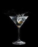 Olijf in een cocktailglas wordt gelaten vallen met vloeistof die Royalty-vrije Stock Afbeeldingen