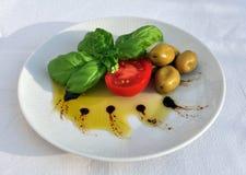 Olijfolie, basilicum, tomaat en groene olijven Royalty-vrije Stock Afbeelding